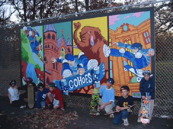 Several kids with skate boards sitting in front of a mural at the skate park.