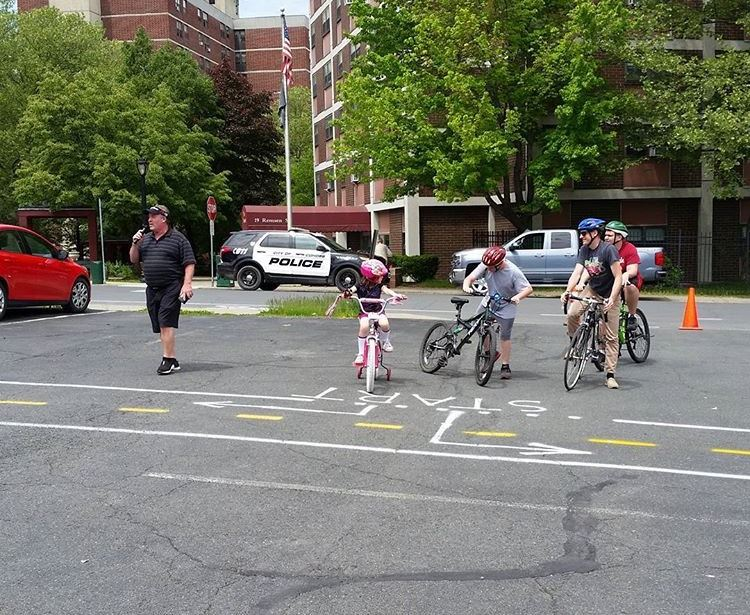 Kids on a bike in a parking lot.