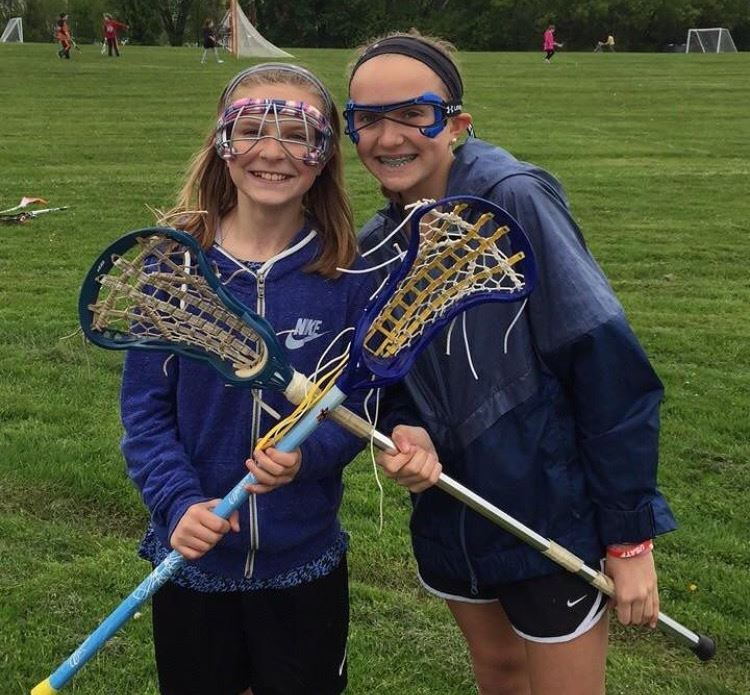 2 girls standing with lacrosse sticks.