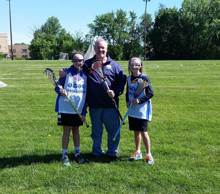 2 girls standing with a lacrosse coach.